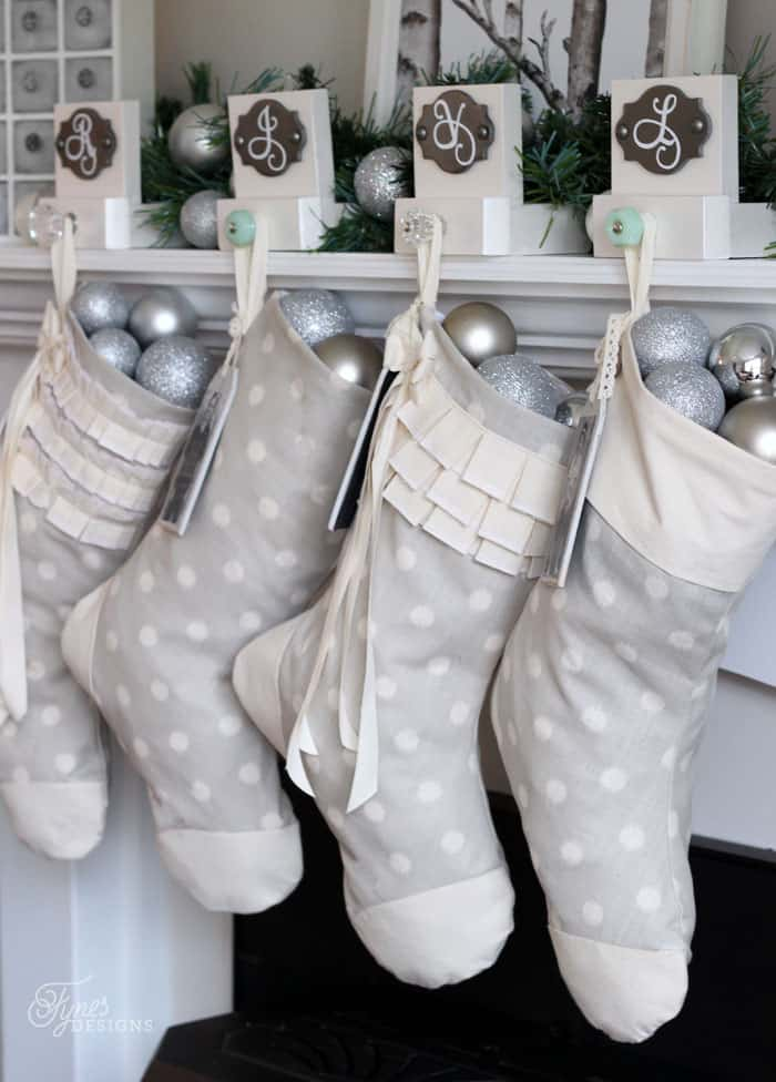 Hand sewn Christmas stocking with easy step by step tutorial  DIY Personalized Christmas Stockings by popular Canada DIY blog, Fynes Designs: image of grey and white stockings filled with silver christmas ornaments and hanging from a white fireplace mantle.