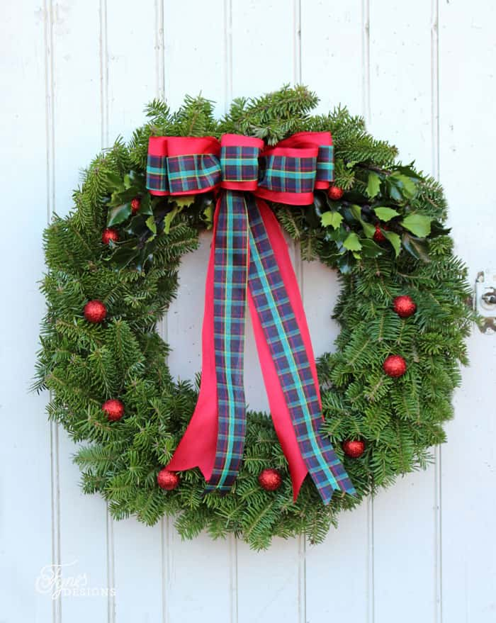 Learn to make a natural balsam fir Christmas wreath with this easy to follow tutorial | Christmas Wreath by popular Canada DIY blog, Fynes Designs: image of a natural Christmas wreath with red glitter berries and red and green plaid bow.