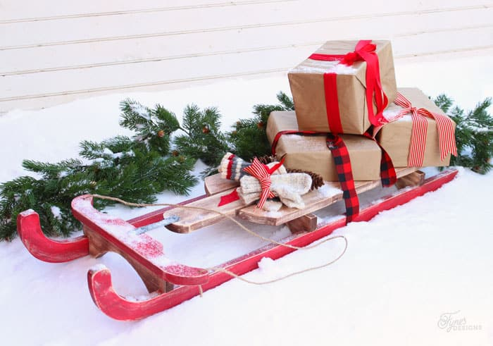 $10 DIY Wooden Sled Tutorial featured by top US craft blog, Fynes Designs: Easy to build $10 Vintage Sled | DIY Wooden Sled by popular Canada DIY blog, Fynes Designs: image of a vintage inspired DIY wooden sled with carrying some brown paper packages tied up in red ribbons and laying in the snow next to an evergreen garland.