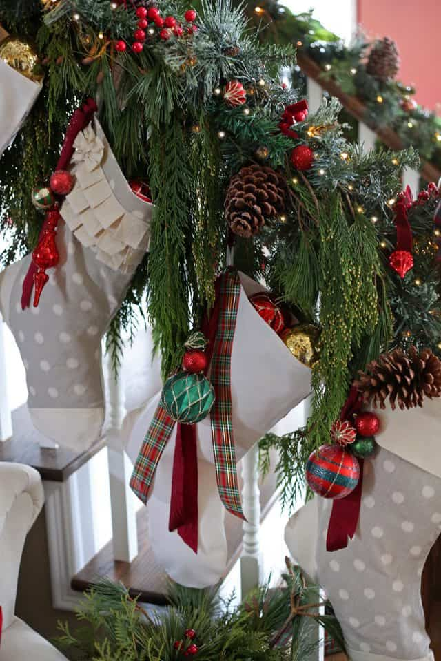 Handmade Christmas stockings hung on the banister with natural garland