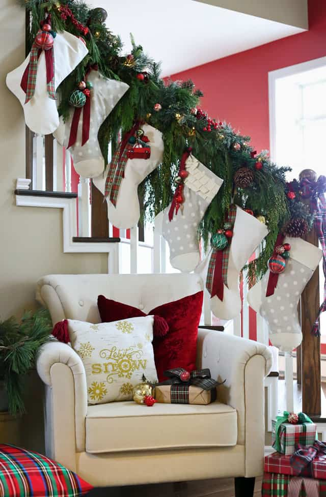 Beautiful handmade Christmas stockings with a free pattern  DIY Personalized Christmas Stockings by popular Canada DIY blog, Fynes Designs: image of grey and white stockings hanging on a stair banister decorated with pine bough garlands, ribbons, pinecones, and red and green Christmas ornaments.
