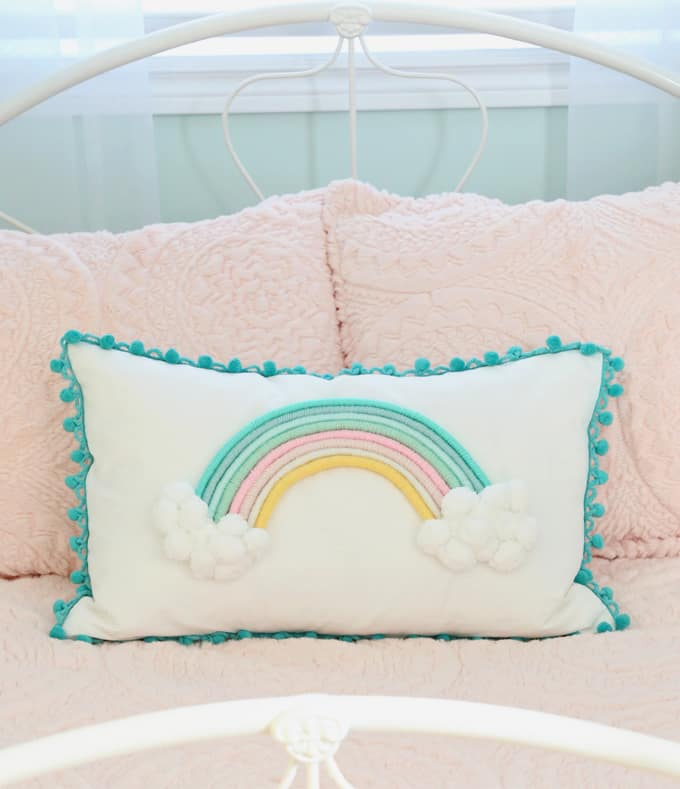 Top 10 Cheap Bedroom Decoration Ideas for Girls featured by top US DIY and interior design blog, Fynes Designs: Hot glue a yarn wrapped rainbow to a pillow for a custom cushion.