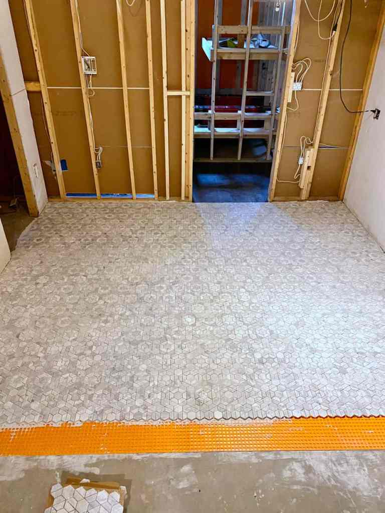 tiling a basement floor with mosaic marble tiles | Jeffrey Court Tile by popular US life and style blog, Fynes Designs: image of a basement with Jeffrey Court Bronson 9-1/2 in. x 11 in. x 8 mm Marble Mosaic Tile.