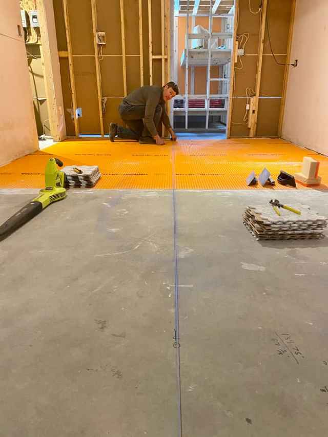 prepping basement floor for Jeffrey Court Bronson Mosaic tile | Jeffrey Court Tile by popular US life and style blog, Fynes Designs: image of a basement getting prepped for tile work.