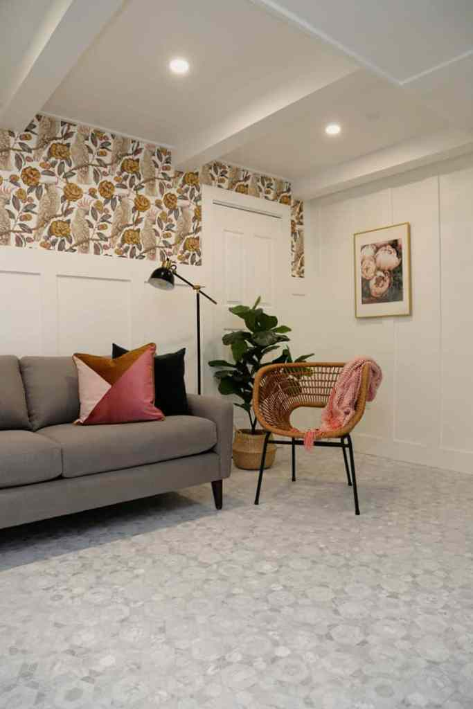 Palm beach styled vacation rental by Virginia or Fynes Designs | effrey Court by popular US interior design blog, Fynes Designs: image of a basement with Jeffrey Court Bronson 9-1/2 in. x 11 in. x 8 mm Marble Mosaic Tile, grey couch with black and multi color throw pillows, wood and metal end table, white board and batten wall, and Photowall Cockatoo Paradise wallpaper.