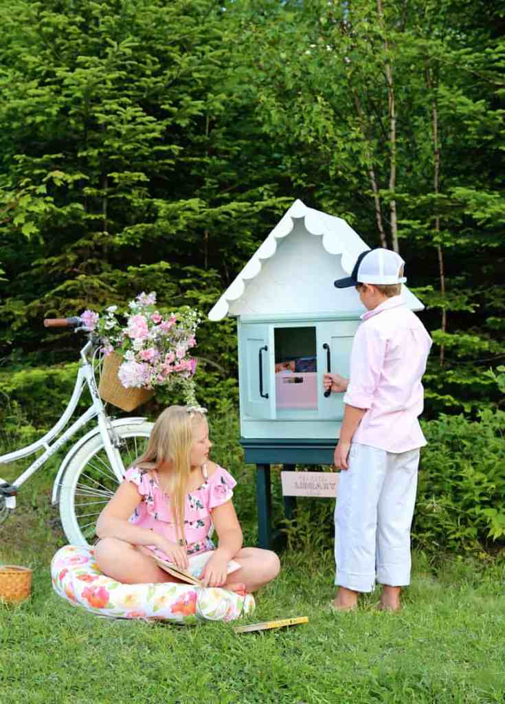 How to build a DIY free little library | Little Free Library Plans by popular US DIY blog, Fynes Designs: image of a free little library next to a beach cruiser bike with a wicker basket full of pink flowers and children sitting on floor pillows while looking at books.