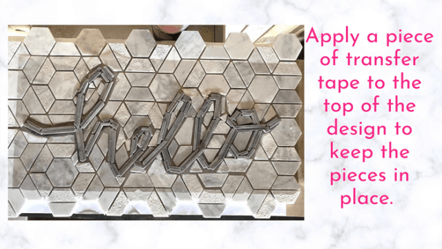 Apply a sheet of transfer tape to your tile lettering design | Tile Lettering by popular US interior design blog, Fynes Designs: image of hello tile lettering being placed on a tile floor.
