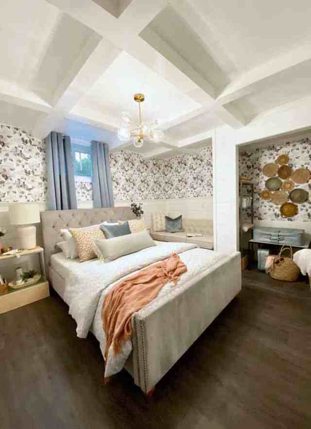 Basement vacation rental master bedroom | Master Bedroom Design by popular Canada interior design blog, Fynes Designs: image of a bedroom with floral wall paper, vinyl plank flooring, modern light fixture, tuft bench, and tufted bed frame.