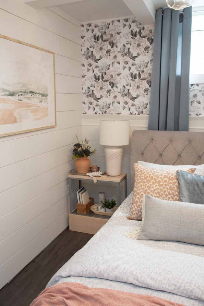 Shiplap in a basement bedroom | Master Bedroom Design by popular Canada interior design blog, Fynes Designs: image of a bedroom with floral wall paper, shiplap walls, blue curtains, modern light fixture, tuft bench, and tufted bed frame.