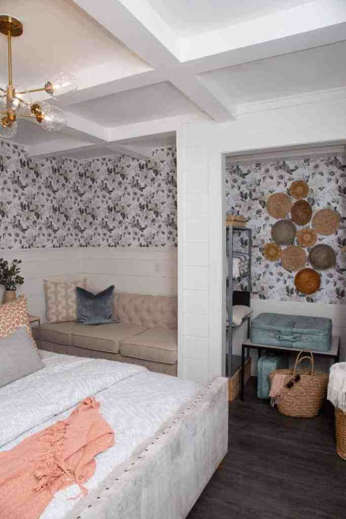 Wallpaper by Roomates Decor in a basement vacation rental | Master Bedroom Design by popular Canada interior design blog, Fynes Designs: image of a bedroom with floral wall paper, vinyl plank flooring, modern light fixture, tuft bench, and tufted bed frame.