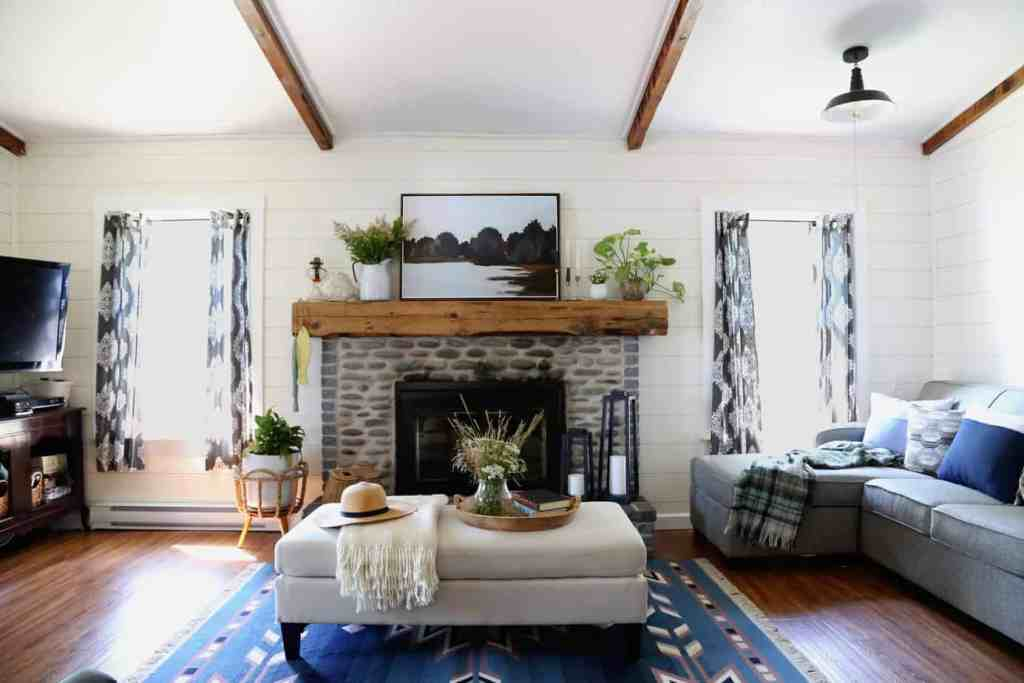 Cottage makeover with an open concept living area |Farmhouse Cottage by popular Canada DIY blog, Fynes Designs: image of a farmhouse cottage living room decorated with blue armchairs, gray sectional couch, black bookshelves, blue accent rug, grey and white curtains, and cream ottoman.