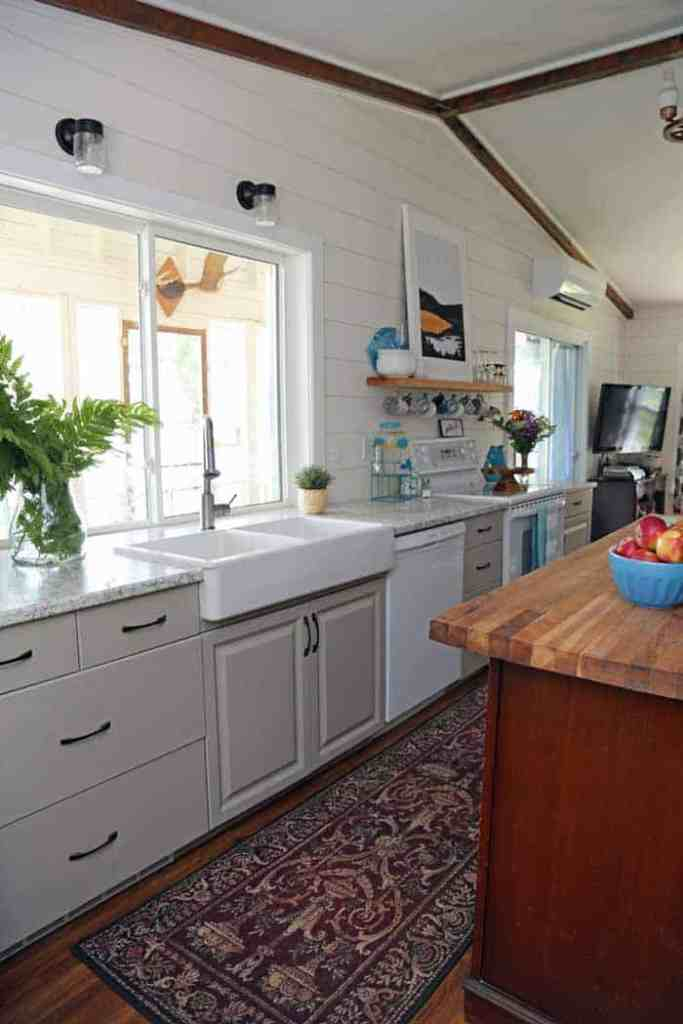 1980's farmhouse cottage kitchen makeover |Farmhouse Cottage by popular Canada DIY blog, Fynes Designs: after image of a 1980's farmhouse cottage kitchen with an apron sink, light grey cabinets, vintage butcher block top island, and modern lighting.