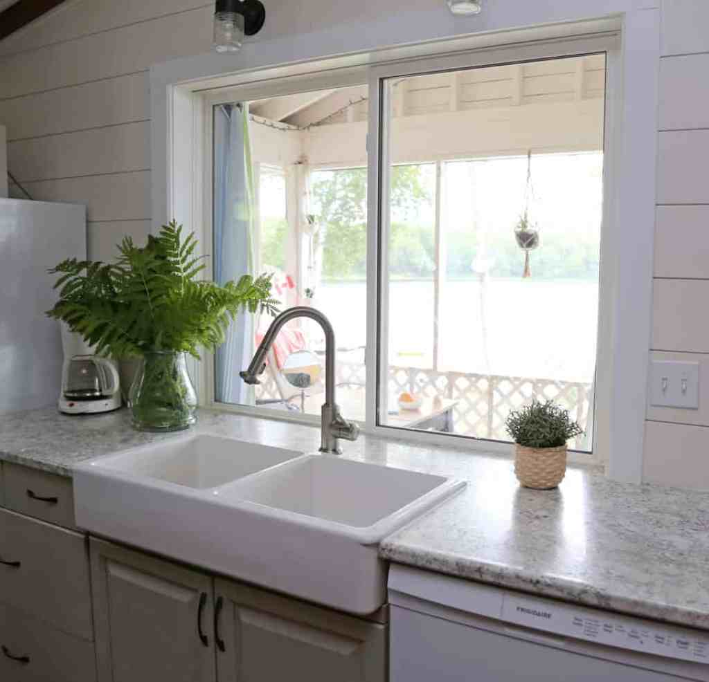 Updated 1980's cottage kitchen |Farmhouse Cottage by popular Canada DIY blog, Fynes Designs: after image of a 1980's farmhouse cottage kitchen with an apron sink, light grey cabinets, and modern lighting.