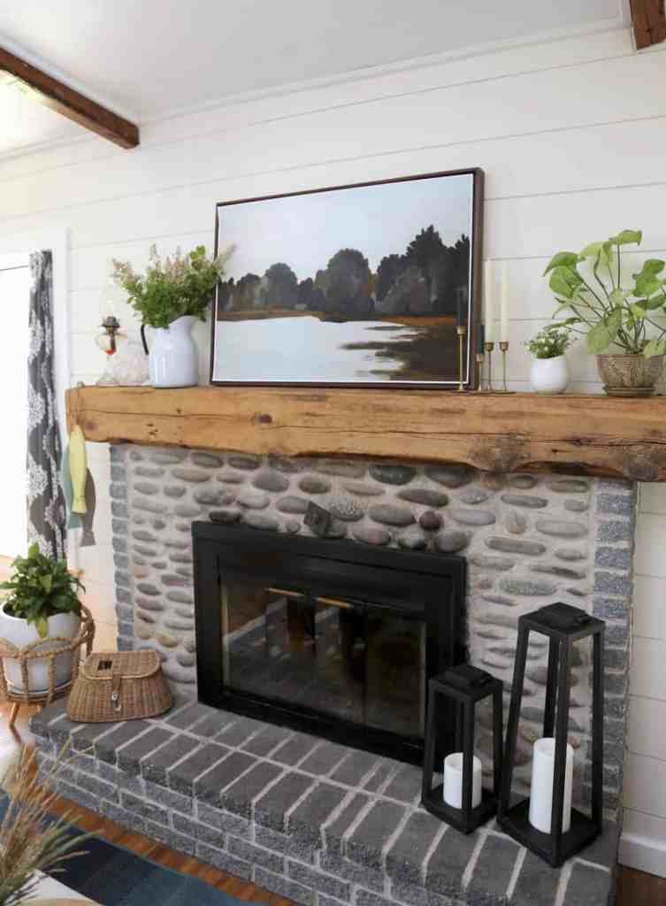 Rustic fireplace mantle in a updated farmhouse cottage makeover.Click to see how a dated 1980s lake house was transformed into a beautiful farmhouse inspired cottage. |Farmhouse Cottage by popular Canada DIY blog, Fynes Designs: image of stone and brick fireplace.