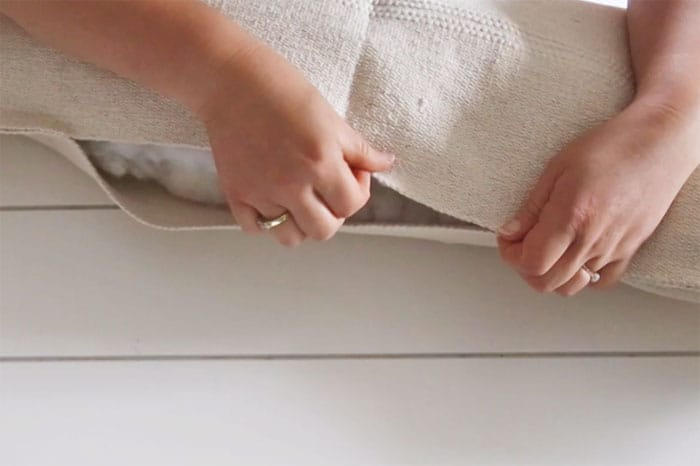 Fill boho pillows with poly fill |  Boho Pillows by popular Canada DIY blog, Fynes Designs: image of a woman making a boho pillow out of a IKEA Sortso rug.