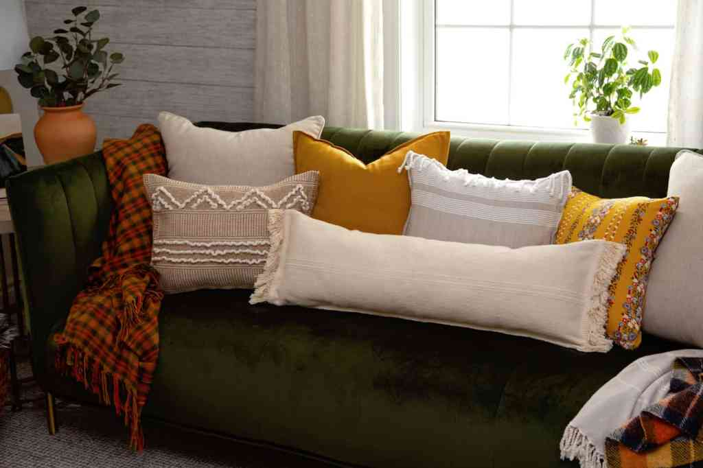 Make cool boho pillows from IKEA rugs | Boho Pillows by popular Canada DIY blog, Fynes Designs: image of various boho pillows on a green velvet couch.