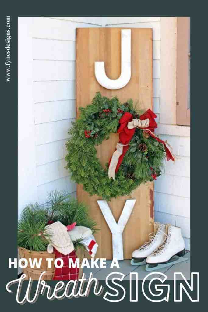 Learn to make a JOY wreath sign for your Christmas porch decorations with this easy to follow tutorial | Joy Sign by popular DIY Canada blog: image of a Joy Wreath sign leaning up against a house next to a pair of white ice skates.