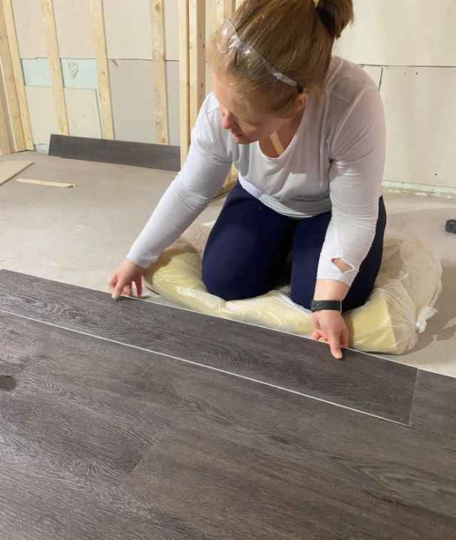 How to put Vinyl Plank Flooring in a basement |Vinyl Plank Flooring by popular Canada interior design blog, Fynes Designs: image of a woman installing vinyl plan flooring in her basement.