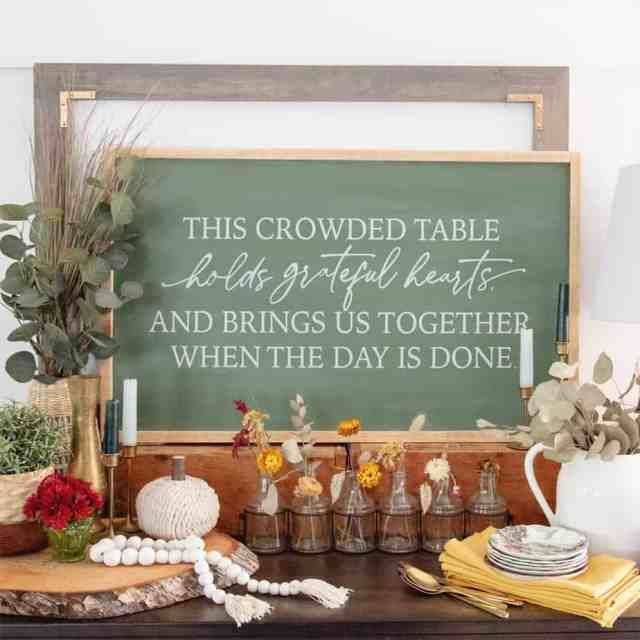 FREE SVG-Thanksgiving dining room art |Thanksgiving decor by popular Canada interior design blog: image of This crowded table chalkboard sign on a dresser decorated with glass bottles, black jars with flowers in them, yellow base lamp, white ceramic pitcher, yellow cloth napkins, and faux green plants.