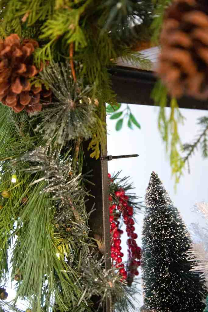 Use cable ties to attach greenery to shelves and banisters |How to Hang Garland by popular Canada DIY blog, Fynes Designs: image of garland attached to a shelf with black cable ties.