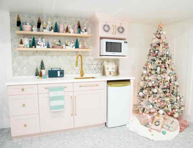 Pink Christmas kitchen |Colorful Christmas Decorations by popular Canada Interior Design blog, Fynes Designs: image of a pink kitchen decorated with a pink, gold, and white Christmas tree, white Christmas village, and Christmas tree decor.