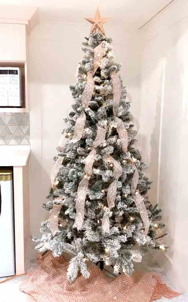 How to put ribbon on a Christmas tree |How to Decorate a Christmas Tree with Ribbon by popular Canada DIY blog, Fynes Designs: image of a flocked Christmas tree decorated with pink ribbon.