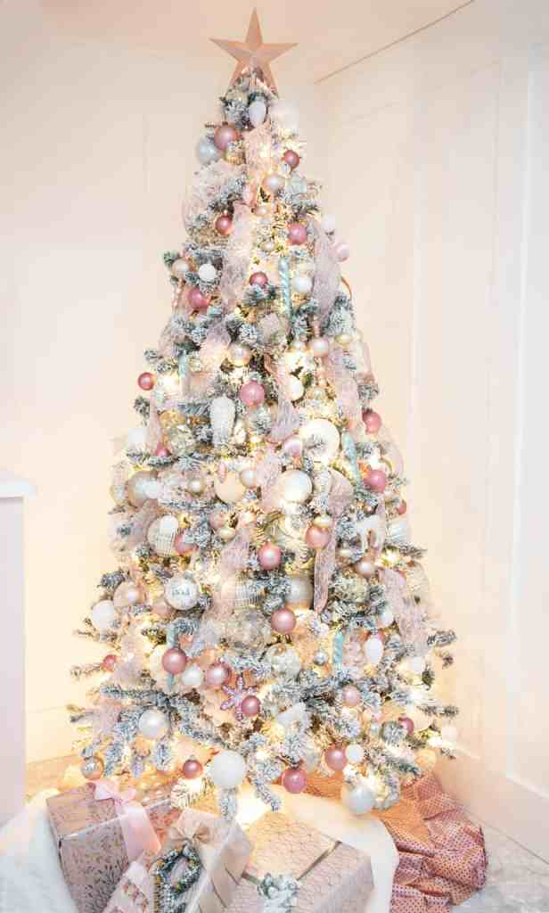 How to put ribbon on a Christmas tree plus other designer tips |How to Decorate a Christmas Tree with Ribbon by popular Canada DIY blog, Fynes Designs: image of a flocked Christmas tree decorated with pink ribbon and pink, gold, rose gold, light blue and white ornaments.