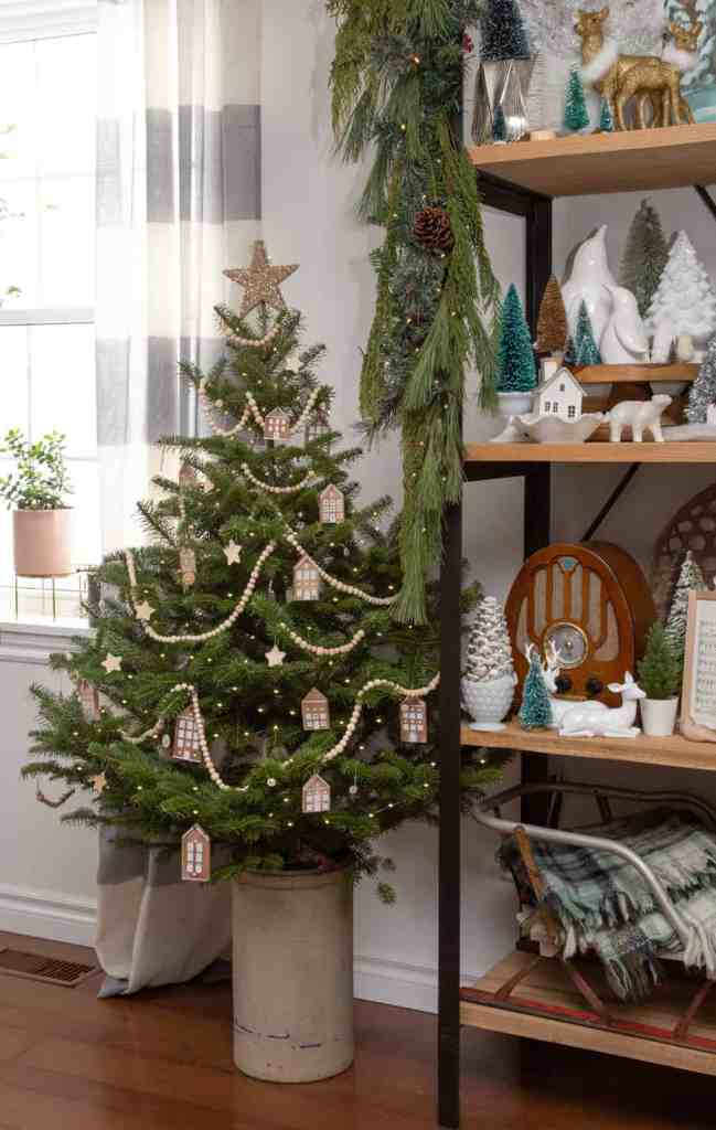 Decorating a small Scandinavian style Christmas tree |Colorful Christmas Decorations by popular Canada Interior Design blog, Fynes Designs: image of a small Christmas tree decorated with wooden houses, wooden stars, and a wooden bead garland.