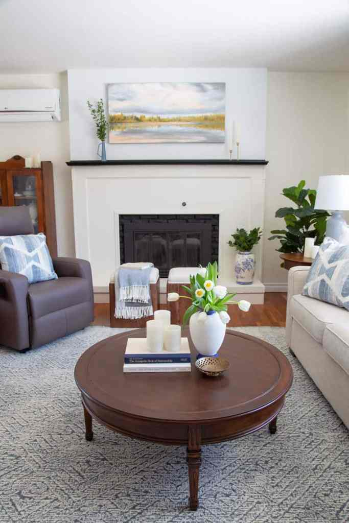 Fireplace makeover- Refresh your fireplace with just paint. Follow these easy DIY instructions to give your dated fireplace a new look.| Living Room Makeover by popular Canada life and style blog, Fynes Designs: image of a living room with a white fireplace, grey recliner chair, cream color couch, blue and white throw pillows, light blue rug, round wooden coffee table, and landscape painting hanging above the fireplace mantle.