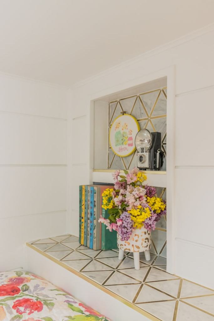 Built in bunk bed wall niche for books and trinkets |  Bunk Room Ideas by popular Canada home design blog, Fynes Designs: image of a built in white marble tile nook with vintage books, vintage camera, vintage cross stitch, and gold and white ceramic planter filled with fresh flowers.