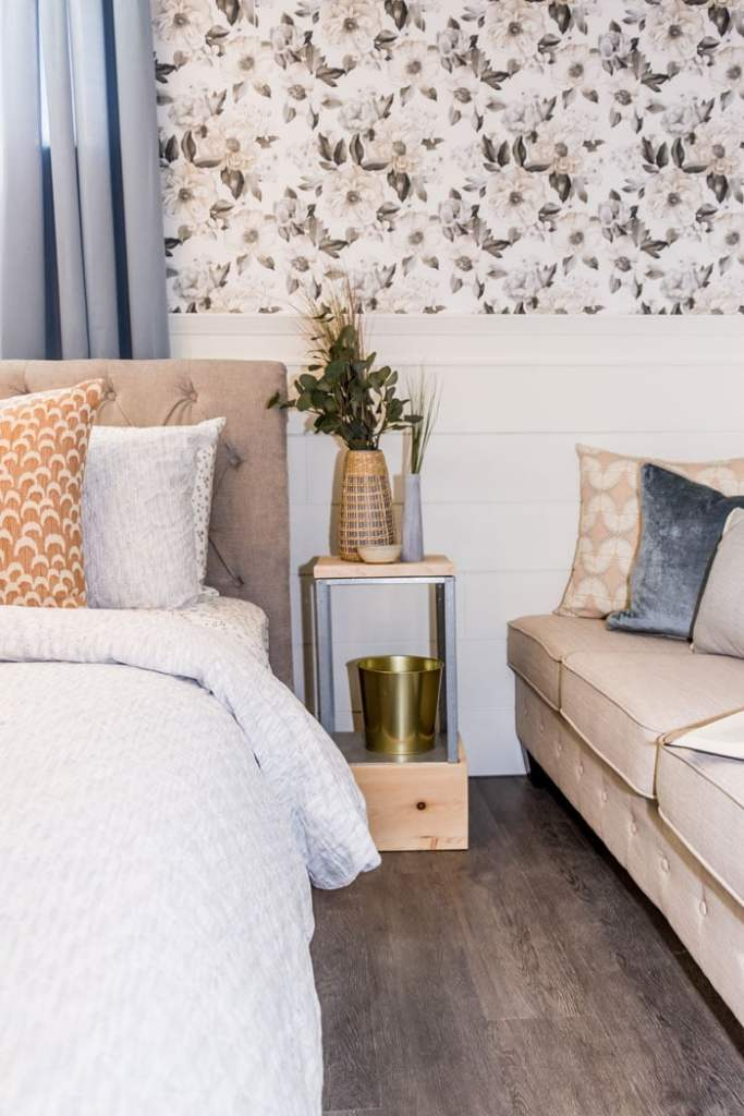 Basement Master bedroom Decorating Ideas |  Bunk Room Ideas by popular Canada home design blog, Fynes Designs: image of a room with a white shiplap wall tan tuft couch, wood and metal side table, and bed with brown tuft fabric headboard with grey, white, and orange, bedding.