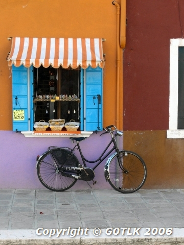 Bicycle next to multi-coloured shop