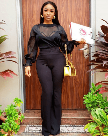 Tonto Dike carrying a gold top handle cc chain bag. The bag is exotic leather