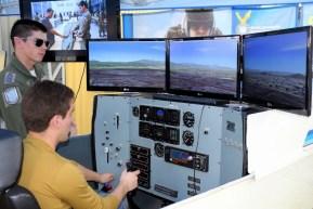 Un cadete de la Fuerza Aérea y un visitante civil explorando el simulador de vuelo del T-35 Pillan (foto: Carlos Ay).
