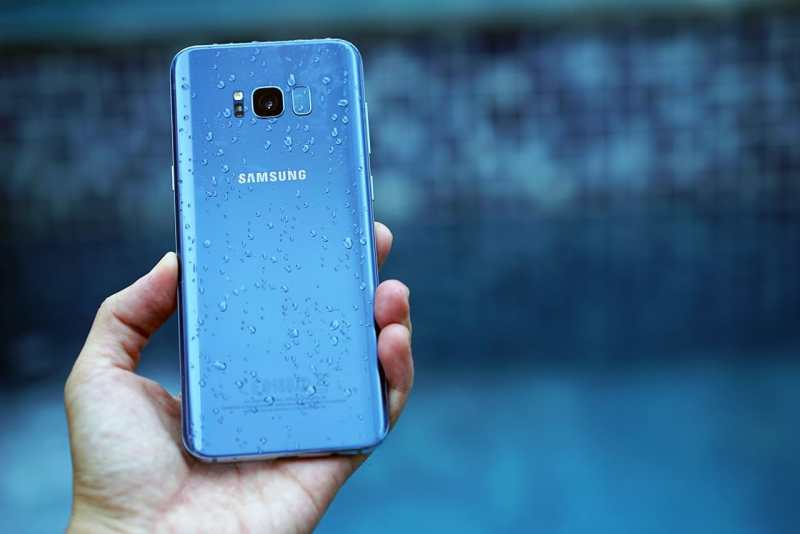 Holding a blue Samsung Galaxy S8 in the rain. It's waterproof!