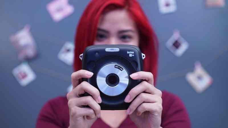 Girl holding Fujifilm Instax SQ10