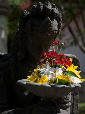 Set in Stone Yogyakarta, Indonesia Amid the hustle and bustle of one of the most populated islands in the world, this statue bows peacefully for eternity. Her flowers are replaced daily by the monks who live and work in the quiet of the monastery.