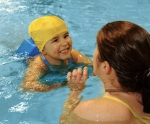 child swimming with adult