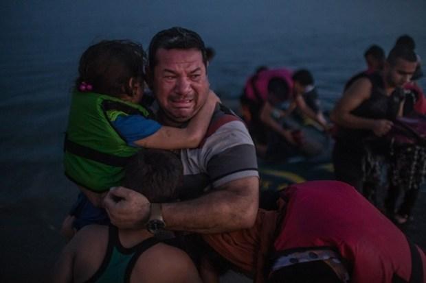 Laith Majid, un iraquí, rompe en llanto mientras abraza a sus hijos tras haber llegado a salvo a Kos, en Grecia, en una endeble embarcación plástica. (Daniel Etter, The New York Times. 15 de agosto de 2015).