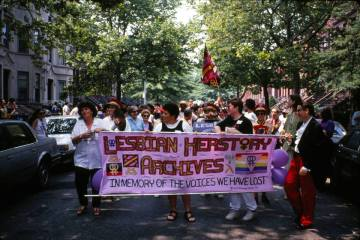 """Photograph of a group of womxn on Lesbian Herstory Archive reopening parade. Womxn are holding a multicoloured banner that reads """"Lesbian Herstory Archives: In memory of those we have lost"""". A band follows them. The photo was taken by Saskia Scheffer on June 20 1993."""