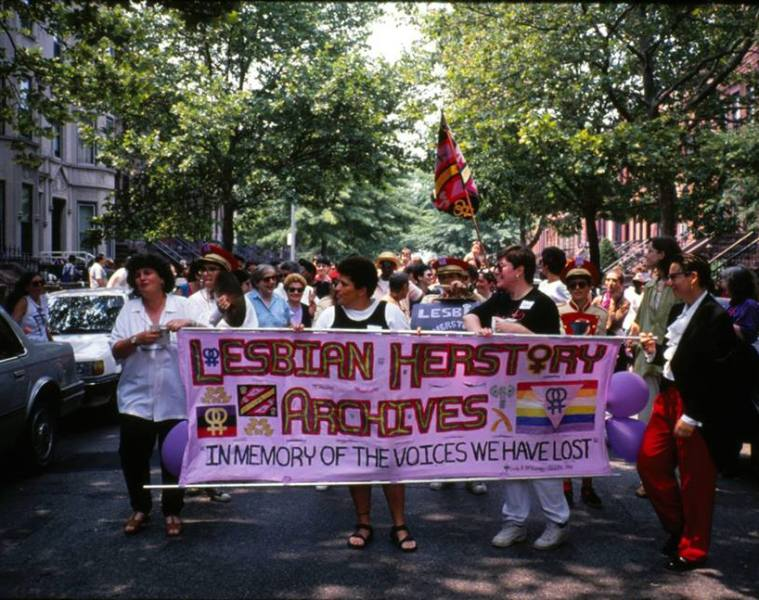 "Photograph of a group of womxn on Lesbian Herstory Archive reopening parade. Womxn are holding a multicoloured banner that reads ""Lesbian Herstory Archives: In memory of those we have lost"". A band follows them. The photo was taken by Saskia Scheffer on June 20 1993."