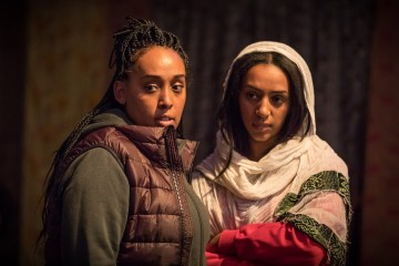 Nahel Tzegai and Sara Mokonen appear as their characters Helene and Rahel in the play 'The Jungle' on London's West End. The image shows the two women side by side, one in a puffa jacket and fleece, the other in a jumper with her hair partially covered by a white scarf. They look to the left of the shot. Photo by Marc Brenner