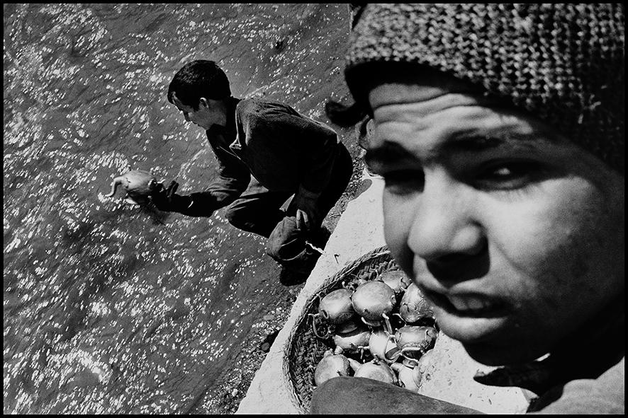 Apprentis dinandiers galvanisant des théières à l'acide dans l'oued Fès 1998