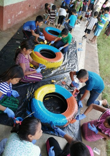 Nenas e nenos pintando neumáticos