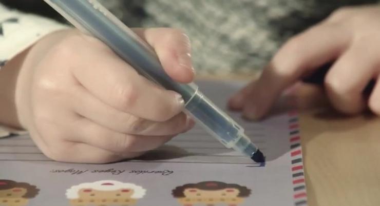 Un neno escribindo unha carta aos Reis