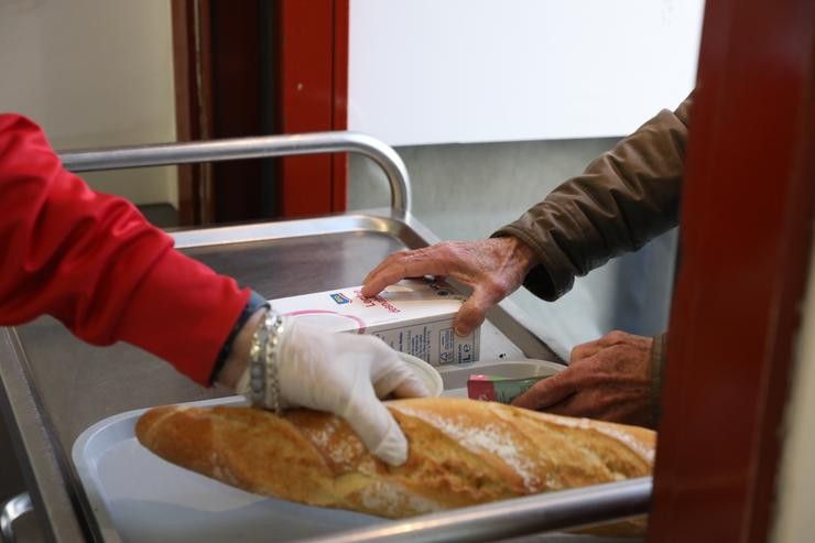 Un voluntario (i) trae comida a unha persoa (d) como parte da repartición diaria de alimentos do Comedor Social San José, en Puente de Vallecas, Madrid