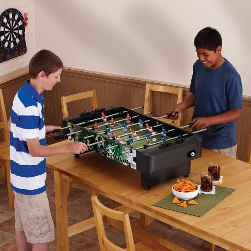 Kids playing mini foosball on a tavle top