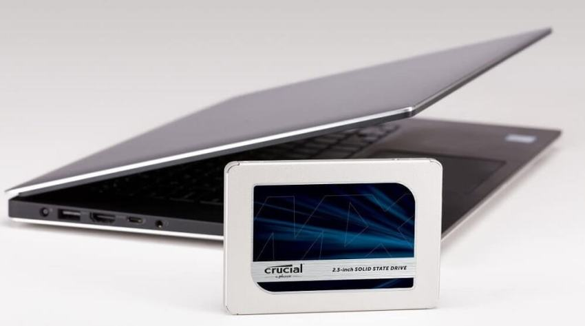 Crucial MX500 SSD placed beside a laptop