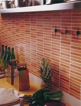 Detalle de pared de la cocina con pequeñas baldosas en tonos anaranjados y rojos.