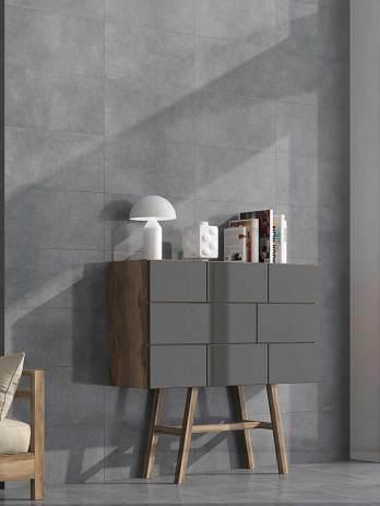Cerámica en despacho; donde se ve una estantería en gris, al igual que la pared.